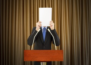 Nervous presenter hides behind sheet of paper